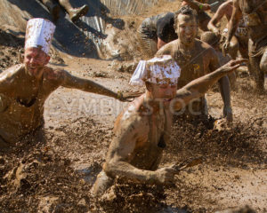 BOISE, IDAHO – AUGUST 25: Runners splash and play in the mud at the Dirty Dash August 25 2012 in Boise, Idaho - Shot Your show