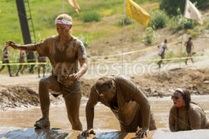 BOISE, IDAHO – AUGUST 25: Runners trying to get over one of the obstacles at the Dirty Dash August 25 2012 in Boise, Idaho - Shot Your show