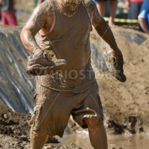 BOISE, IDAHO – AUGUST 25: Unidentified runner walks without his shoes at the Dirty Dash August 25 2012 in Boise, Idaho - Shot Your show