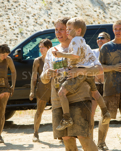 BOISE, IDAHO – AUGUST 25: Unidentified woman holding her child covered in mud at the Dirty Dash August 25 2012 in Boise, Idaho - Shot Your show