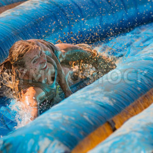 BOISE, IDAHO – AUGUST 25: Unidentified woman slides with a huge smile at the Dirty Dash August 25 2012 in Boise, Idaho - Shot Your show