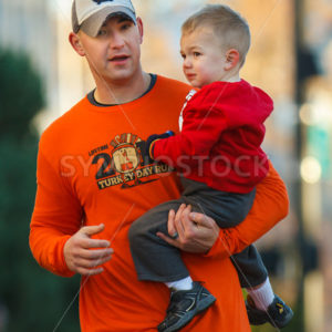 BOISE, IDAHO – NOVEMBER 22:  Man holds his son while competing in The 5k Turkey Day race in Boise, Idaho on November 22, 2012 - Shot Your show