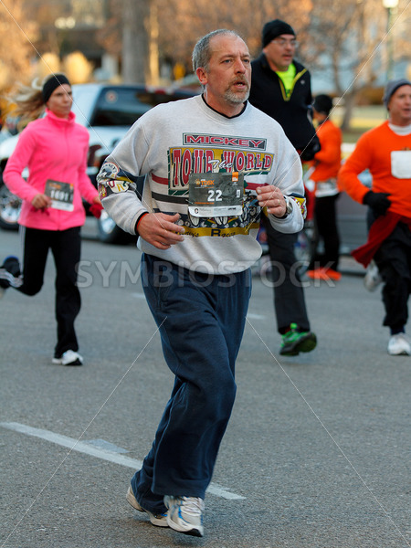 BOISE, IDAHO – NOVEMBER 22:  Man with the bib number 22 runs with a crowd of people during the Turkey Day 5k in Boise, Idaho on November 22, 2012 - Shot Your show