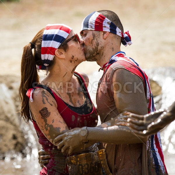 BOISE, IDAHO/USA – AUGUST 11, 2013: Couple proud of their recent success at finishing and celebrat with a kiss at the DIrty Dash in Boise, Idaho - Shot Your show