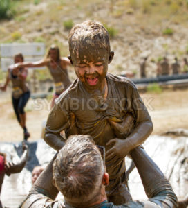 BOISE, IDAHO/USA – AUGUST 11, 2013: Father holds up his proud son during the Dirty Dash in Boise, Idaho - Shot Your show