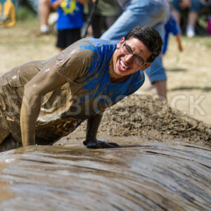 BOISE, IDAHO/USA – AUGUST 11, 2013: Man at the finish doing the last obstacle at the Dirty Dash in Boise, Idaho - Shot Your show