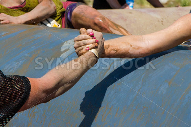 BOISE, IDAHO/USA – AUGUST 11, 2013: Man grabs the hand of a woman to help her at the dirty dash in Boise, Idaho - Shot Your show