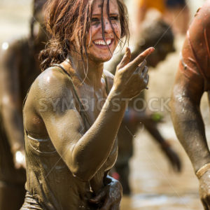 BOISE, IDAHO/USA – AUGUST 11, 2013: Unidentified woman smiles and points near the finish at the dirty dash - Shot Your show