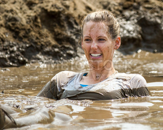 BOISE, IDAHO/USA – AUGUST 11, 2013: Woman tries to relax in the mud near the end of the race at the dirty dash - Shot Your show