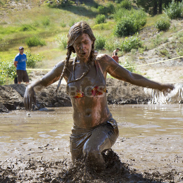 BOISE, IDAHO/USA – AUGUST 11, 2013: woman running through to the finish at the Dirty Dash in Boise, Idaho - Shot Your show