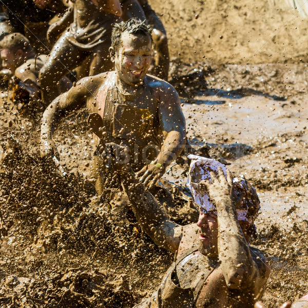 BOISE, IDAHO/USA – AUGUST 25 – Group of people play in the mud making a big splash  The Dirty dash is a 10k run through obstacles and mud on August 25, 2012 in Boise, Idaho - Shot Your show