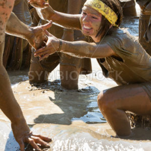 BOISE, IDAHO/USA – AUGUST 25 – Unidentified woman is helped up out of the mud during the dirty dash.  The Dirty dash is a 10k run through obstacles and mud on August 25, 2012 in Boise, Idaho - Shot Your show