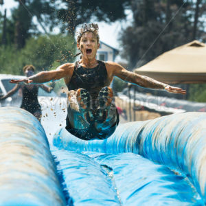BOISE, IDAHO/USA – AUGUST 25 – Unidentified woman jumps down a slide getting air time. The Dirty dash is a 10k run through obstacles and mud on August 25, 2012 in Boise, Idaho - Shot Your show