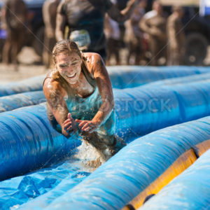 BOISE, IDAHO/USA – AUGUST 25 – Unidentified woman jumps to go down the slide. The Dirty dash is a 10k run through obstacles and mud on August 25, 2012 in Boise, Idaho - Shot Your show
