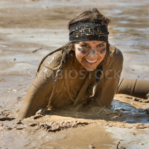 BOISE, IDAHO/USA – AUGUST 25 –  Unidentified woman smiles at the camera while she runs the Dirty Dash August 25, 2012 in Boise, Idaho - Shot Your show