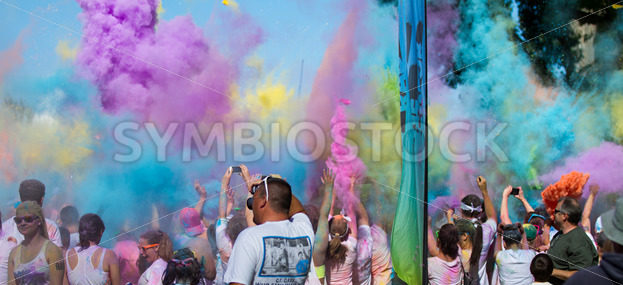 BOISE, IDAHO/USA – JUNE 22: Color bombs are being thrown into the air by the crowd at the Color Me Rad 5k in boise on June 22, 2013 - Shot Your show