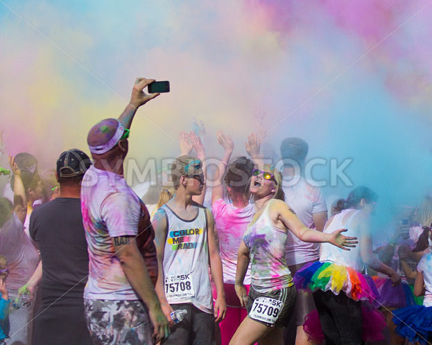BOISE, IDAHO/USA – JUNE 22: Unidentified man takes a photo of another runner and all the colors at the Color Me Rad 5k in boise on June 22, 2013 - Shot Your show