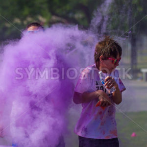 BOISE, IDAHO/USA – JUNE 22: Young runner making just getting pelted with a color bomb at the Color Me Rad 5kin boise on June 22, 2013 - Shot Your show
