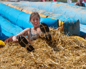 BOISE, IDAHO/USA - AUGUST 10, 2013: Unidentified woman crashes into the hay at the end of the slide during the The Dirty Dash - Shot Your show