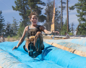 BOISE, IDAHO/USA - AUGUST 10, 2013: Unidentified woman jumps on the slide while making an interesting facial expression at the The Dirty Dash - Shot Your show