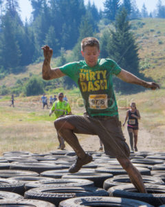 BOISE, IDAHO/USA - AUGUST 10: A runner with bib number 9736 does tries his luck through the tire obstacles at the The Dirty Dash in Boise, Idaho on August 10, 2013  - Shot Your show