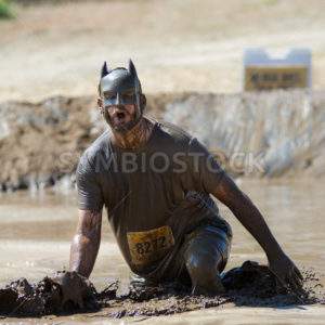 BOISE, IDAHO/USA - AUGUST 10: Man 8272 wearing a batman mask splashes mud at the finish line. This race took place at the The Dirty Dash in Boise, Idaho on August 10, 2013  - Shot Your show