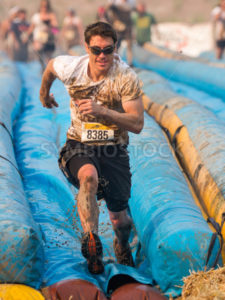 BOISE, IDAHO/USA - AUGUST 10: Person 8385 runs down the slide full speed at the The Dirty Dash in Boise, Idaho on August 10, 2013  - Shot Your show