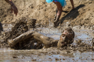BOISE, IDAHO/USA - AUGUST 10: Person swims through the mud pond on his way to the finish line at the The Dirty Dash in Boise, Idaho on August 10, 2013 - Shot Your show