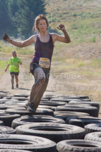 BOISE, IDAHO/USA - AUGUST 10: Runner 10951 steps over the tires during one of the obstacles at the The Dirty Dash in Boise, Idaho on August 10, 2013 - Shot Your show