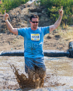 BOISE, IDAHO/USA - AUGUST 10: Runner 40518 makes a small splash while throwing up the devil horns at the The Dirty Dash in Boise, Idaho on August 10, 2013  - Shot Your show