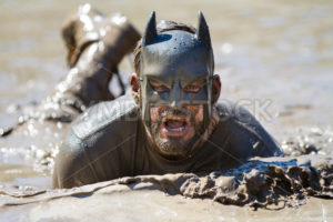 BOISE, IDAHO/USA - AUGUST 10: Runner dressed as batman swims in the mud during the The Dirty Dash in Boise, Idaho on August 10, 2013  - Shot Your show