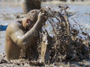 BOISE, IDAHO/USA - AUGUST 10: Unidentified man washes off using mud at the The Dirty Dash in Boise, Idaho on August 10, 2013  - Shot Your show