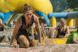BOISE, IDAHO/USA - AUGUST 10: Unidentified runner on her knees as she climbs over an obstacle at the The Dirty Dash in Boise, Idaho on August 10, 2013 - Shot Your show
