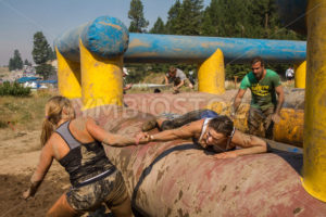 BOISE, IDAHO/USA - AUGUST 10: Unidentified woman helps out another over an obstacle at the The Dirty Dash in Boise, Idaho on August 10, 2013 - Shot Your show