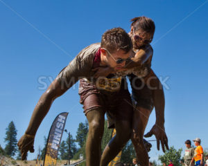 BOISE, IDAHO/USA - AUGUST 10: Unidentified woman is getting off the back of runner 40429 at the The Dirty Dash in Boise, Idaho on August 10, 2013  - Shot Your show