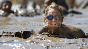 BOISE, IDAHO/USA - AUGUST 10: Unidentified woman pokes her head up from the mud while wearing goggles at the The Dirty Dash in Boise, Idaho on August 10, 2013  - Shot Your show