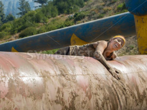 BOISE, IDAHO/USA - AUGUST 10: Unidentified woman tries to climb over an obstacle with a smile on her face at the The Dirty Dash in Boise, Idaho on August 10, 2013 - Shot Your show