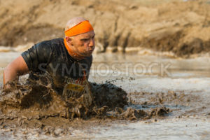 BOISE, IDAHO/USA - AUGUST 10:Runner 40119 splashes hard through the mud determined to finish at the The Dirty Dash in Boise, Idaho on August 10, 2013  - Shot Your show