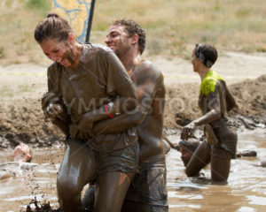 BOISE, IDAHO/USA - AUGUST 11, 2013: Unidentified man picks up a woman during the race at the dirty dash - Shot Your show