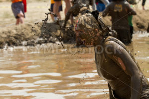 BOISE, IDAHO/USA - AUGUST 11, 2013: Unidentified woman gets a splash of mud thrown her way at the dirty dash - Shot Your show