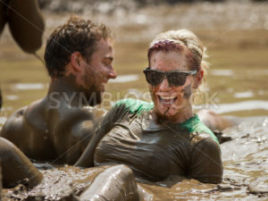 BOISE, IDAHO/USA - AUGUST 11, 2013: Unidentified woman laughing while sitting in the mud at the dirty dash - Shot Your show
