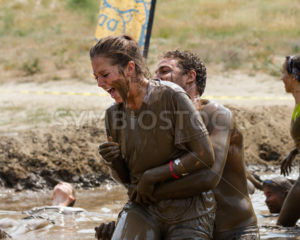 BOISE, IDAHO/USA - AUGUST 11, 2013: Woman tries to relax in the mud near the end of the race at the dirty dash - Shot Your show