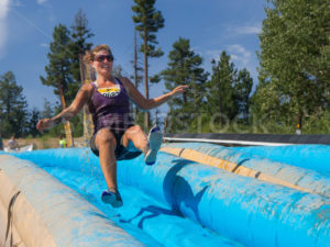 BOISE, IDAHO/USA - AUGUST 11: Runner 9682 jumps on the slide on her way to the finish line at the The Dirty Dash in Boise, Idaho on August 11, 2013  - Shot Your show