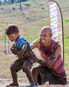 BOISE, IDAHO/USA - AUGUST 11: Unidentified man helps a child up near the finish line of the The Dirty Dash in Boise, Idaho on August 11, 2013  - Shot Your show