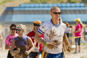BOISE, IDAHO/USA - AUGUST 25 - Crowd runs during the Dirty Dash covered in mud. The Dirty dash is a 10k run through obstacles and mud on August 25, 2012 in Boise, Idaho - Shot Your show