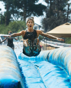 BOISE, IDAHO/USA - AUGUST 25 - Unidentified woman jumps down a slide getting air time. The Dirty dash is a 10k run through obstacles and mud on August 25, 2012 in Boise, Idaho - Shot Your show
