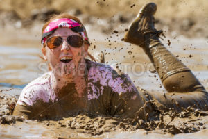 BOISE, IDAHO/USA - AUGUST 25 -  Woman playing in the mud at the dirty dash. The Dirty dash is a 10k run through obstacles and mud on August 25, 2012 in Boise, Idaho - Shot Your show