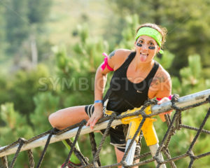 BOISE, IDAHO/USA - AUGUST 8, 2014: Unidentified woman climbs over the ropes  sticking out her tongue at the Dirty Dash in Boise, Idaho - Shot Your show
