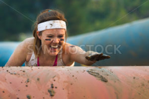 BOISE, IDAHO/USA - AUGUST: Unidentified woman climbs over an obstacle at the The Dirty Dash in Boise, Idaho on August , 2013  - Shot Your show