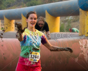 BOISE, IDAHO/USA - AUGUST: Unidentified woman throws some mud at the The Dirty Dash in Boise, Idaho on August , 2013  - Shot Your show